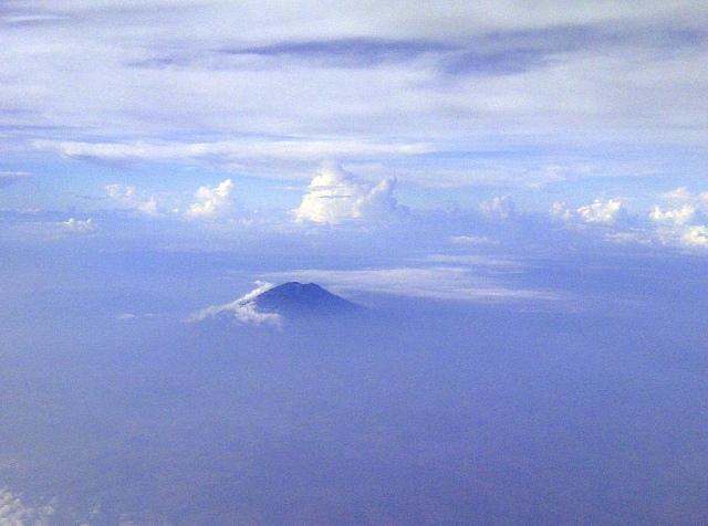 Sebuah gunung menyembul di atas awan. entah gunung apa.
