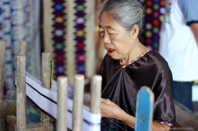An old women is carefully starting a peace of woven fabric using traditional tools